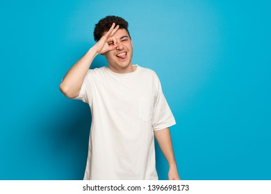 Young man over blue background makes funny and crazy face emotion