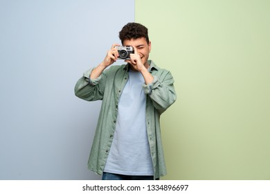 Young man over blue and green background holding a camera