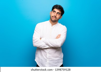 Young man over isolated blue wall with confuse face expression while bites lip