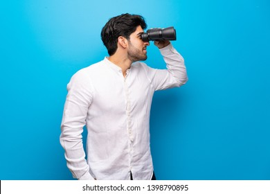 Young man over isolated blue wall and looking in the distance with binoculars
