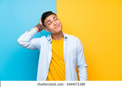 Young man over isolated colorful background having doubts and with confuse face expression