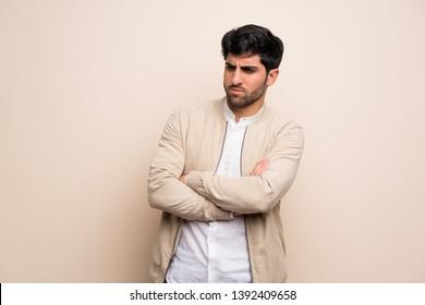 Young man over isolated wall feeling upset