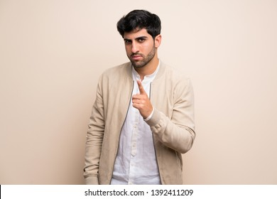 Young man over isolated wall frustrated and pointing to the front
