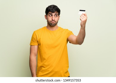 Young man over pink wall taking a credit card without money