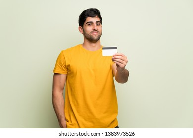Young man over pink wall holding a credit card