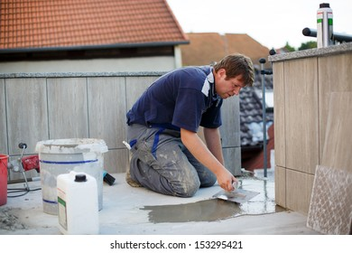 Young man in overall tiling on balcony ceramic tiles