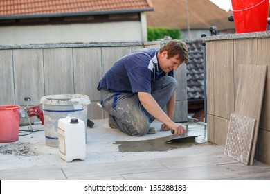 Young man in overall tiling on balkony ceramic tiles