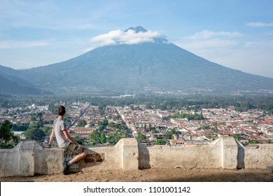 Young man overlooking Antigua Guatemala and volcano from viewpoint