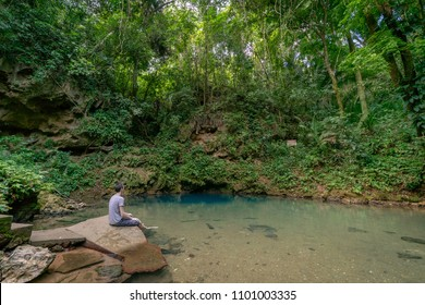 Young man overlooking Blue Hole national park swimming spot in Belize