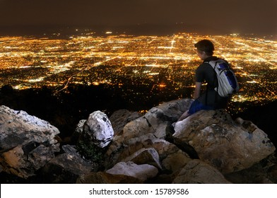 Young man overlooking Salt Lake City from Mount Olympus at night