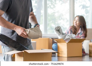 Young man packing cloth into cardboard box prepare to move out to new location.
