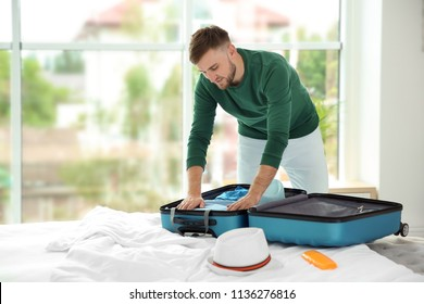 Young man packing suitcase for summer journey on bed
