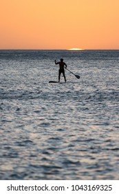 young man paddle boarding in the pacific ocean in Nicaragua as the sun sets behind him