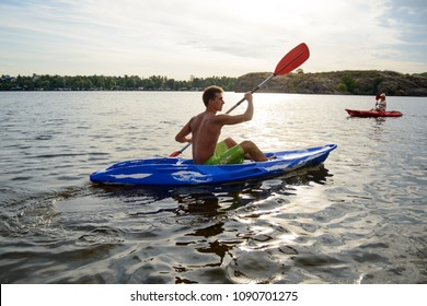 Young Man Paddling Kayak on the Beautiful River or Lake under the Dramatic Evening Sky at Sunset