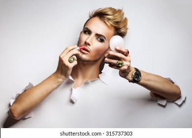 a young man painted female cosmetics