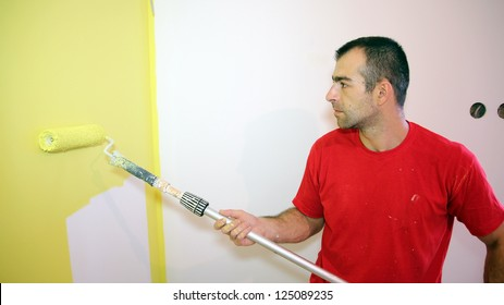 Young Man Painting Apartment. Decorator using a long roller to paint a wall in yellow.