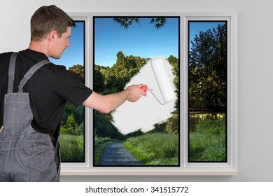 A young man is painting a window with a white color.