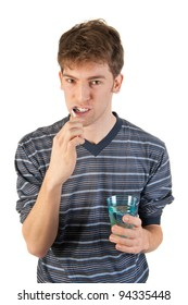 Young man in pajamas is brushing his teeth