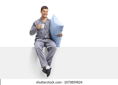 Young man in pajamas holding a cup and a pillow seated on a panel isolated on white background