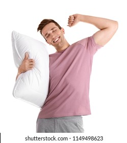 Young man in pajamas with pillow on white background