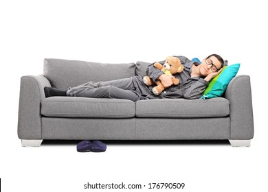 Young man in pajamas sleeping on couch with teddy bear isolated on white background