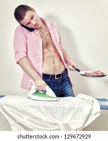 Young man with pan and phone ironing his shirt