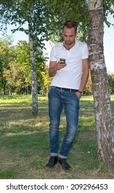 Young man  in the park with cell phone in hand