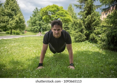 young man in park doing push ups