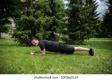 young man in park exercising in plank