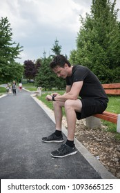 young man in park looking at stopwatch