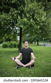 young man in park meditating on grass