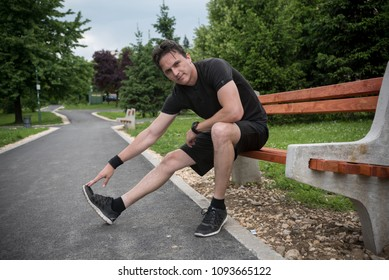 young man in park stretching leg while sitting on bench