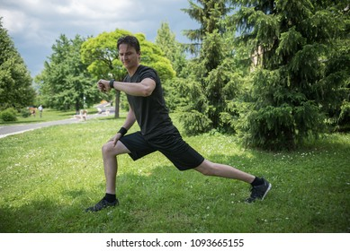 young man in park stretching and looking at watch