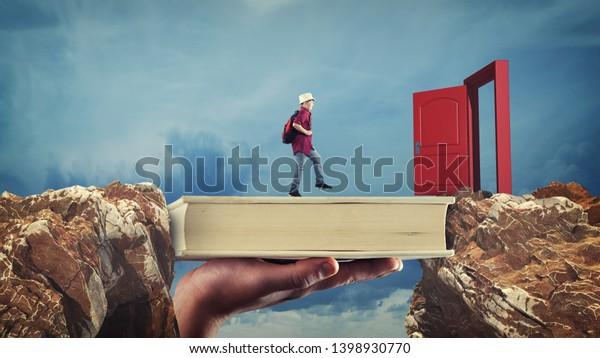 Der junge Mann geht von einem Gipfel zum anderen über ein Buch. Geöffnete Tür. Das Konzept von Stipendium und Chance.