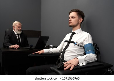 Young man passing check with lie detector, sitting on black chair. Sensors with wires on fingers of hands and chest. Elderly expert examinating man with computer polygraph and defining lie or truth.