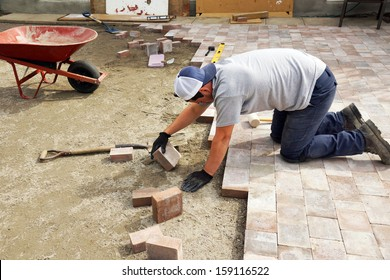 Young man paving or laying down paver as part of landscaping