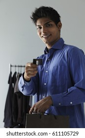 young man paying with credit card in shop