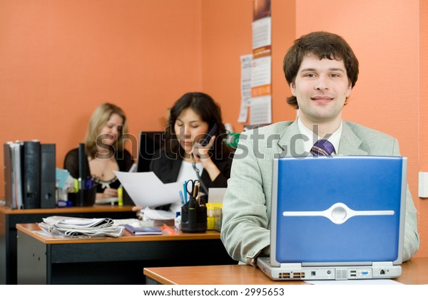 A young man with people working at the office