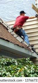 Young man perches on metal ladder on roof top.  He is installing siding on his home.  He is wearing a tool belt, red shirt and work jeans.