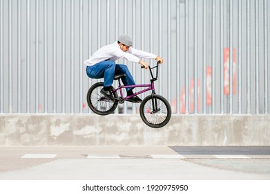 Young man performing tricks with a flatland bmx bike