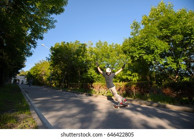 A young man performs a complicated stunt on a longboard