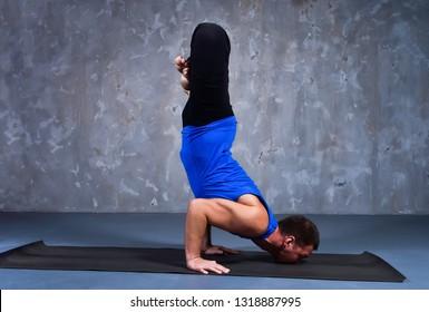 Young man performs the pose of yoga Urdhva padma vrikshasana