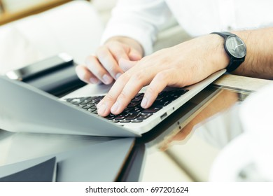 Young man performs work on a laptop