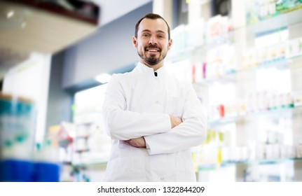 Young man pharmacist displaying assortment of drugs in pharmacy
