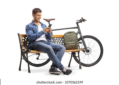 Young man with a phone and a bicycle sitting on a wooden bench isolated on white background