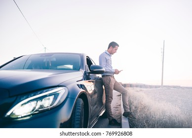 Young man phone poses with his car.