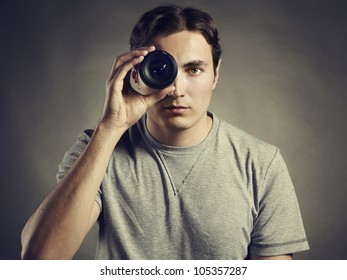 Young man photographer holding a lens in his eye. Lens as eye