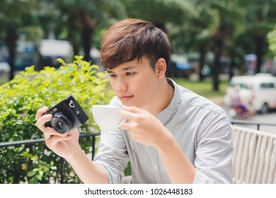 Young man photographer taking picture sitting at table in coffee shop