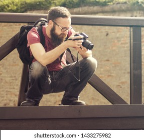 Young man photographer taking pictures with SLR camera, capture old town beauty