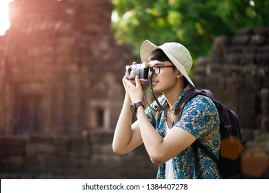 Young Man Photographer Traveler with backpack taking photo with his retro film camera, Great wall in background at historical place. Lifestyle and travel concept.